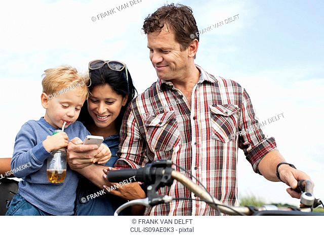 Family looking at smartphone and having a drink