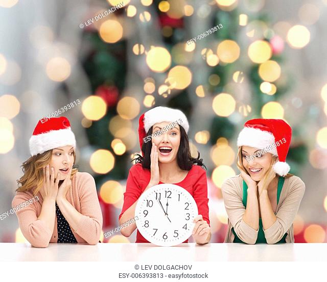 winter, holidays, time and people concept - smiling women in santa helper hats with clock over christmas tree background