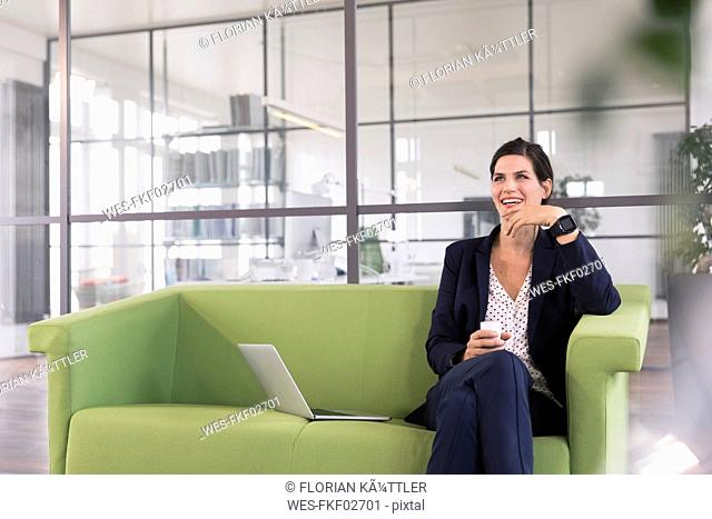 Businesswoman with laptop sitting on a couch and drinking coffee in the office