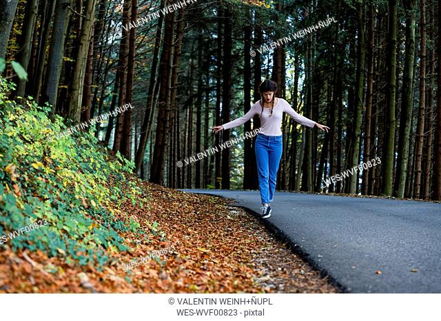 Young woman balancing at roadside in the woods
