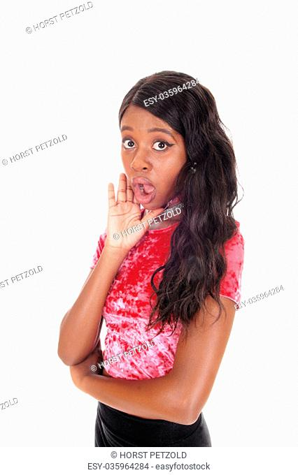 A beautiful African woman standing with her mouth open surprised.with her hand on her face, isolated for white background