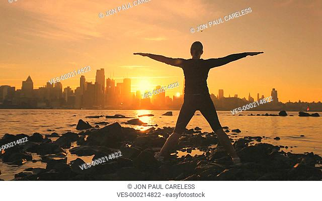 Silhouette eines Menschen, der am Strand, bei Sonnenuntergang, Yoga?bungen macht