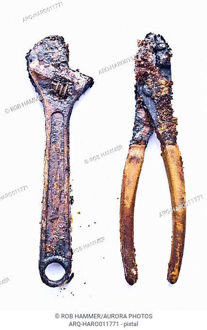 Adjustable wrench and pliers covered with rust against white background