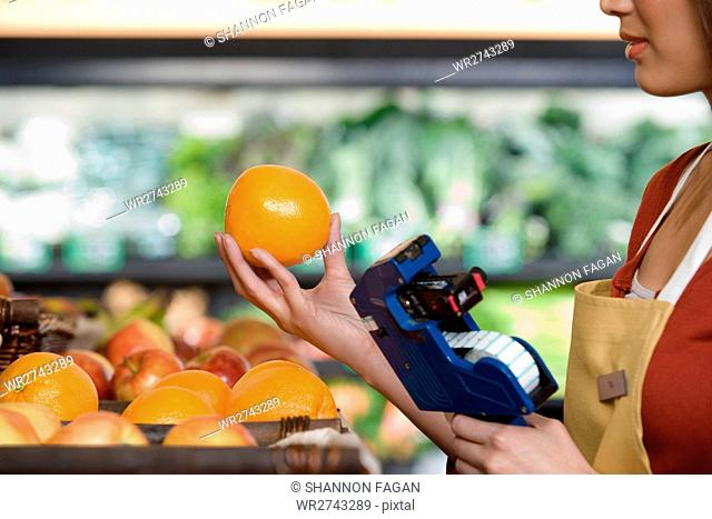 sales assistant pricing an orange
