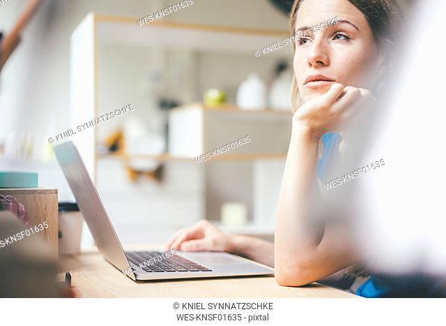 Young woman using laptop at desk at home
