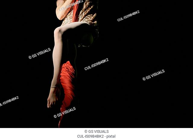 Waist down view of young female aerial acrobat wrapped around silk rope