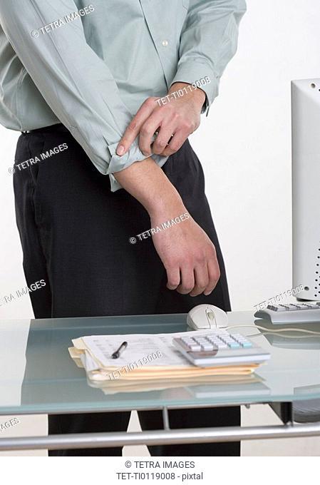 Man at desk rolling up his shirt sleeves