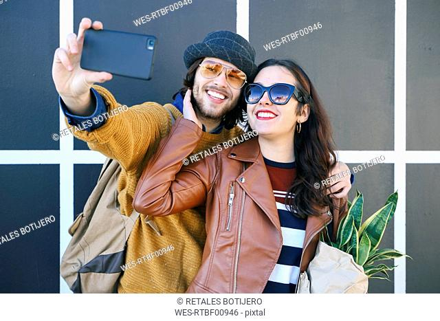 Happy young couple taking selfie with smartphone