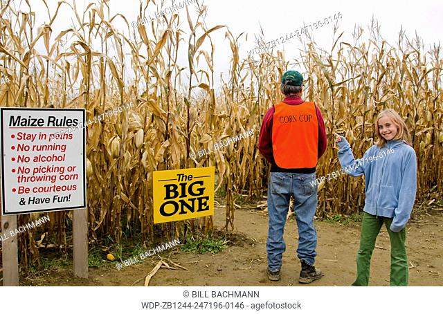 Farmington Maine fall activity Corn Maze in field with corn stalks and man in charge with young girl pointing called Corn Cop in Northern New England in October