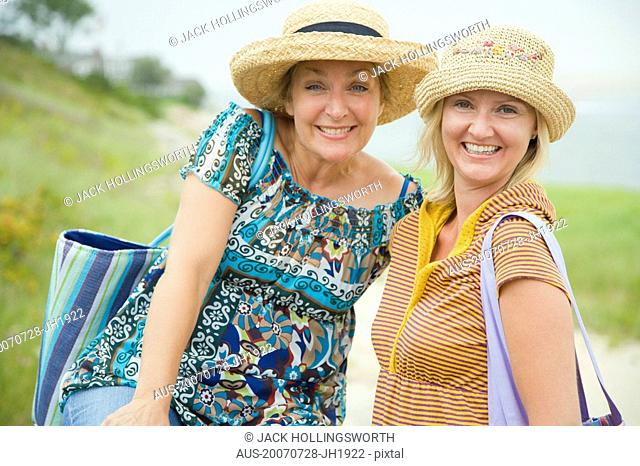 Portrait of a mid adult woman and a mature woman wearing a straw hat and smiling