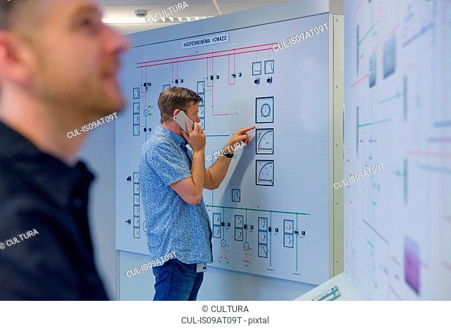 Engineer pointing at control panel whilst using smartphone at geothermal power station