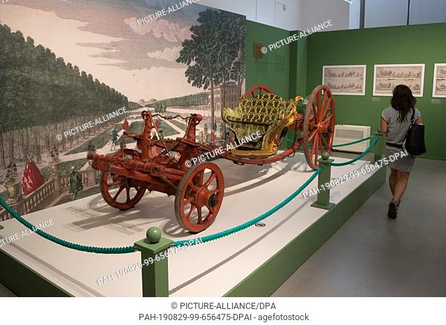"""29 August 2019, Saxony, Dresden: A woman walks past a park car from 1680 as part of a press tour of the traffic museum in the exhibition """"""""Von Prunkgondeln"""