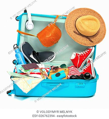 The open blue suitcase, sneakers, clothing, hat, and retro camera on white background. The travel, tourism and holidays concept