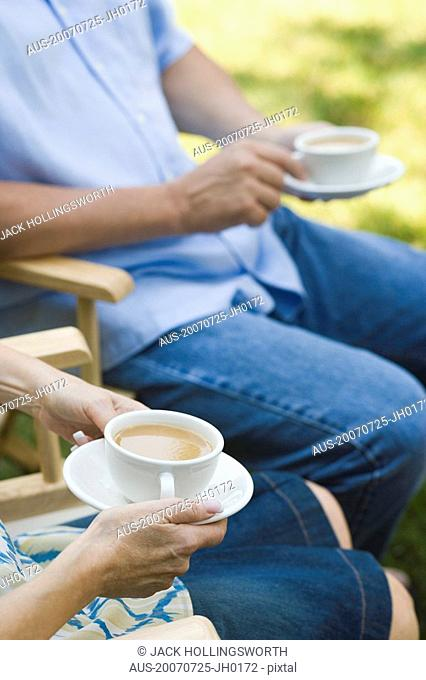Mid section view of a mature couple holding tea cups