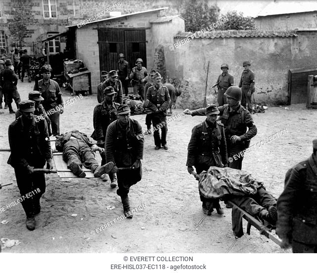 German prisoners carry their fallen comrades for burial at Brehal, France. Guarded by U.S. Military Police, the POW's were captured during the U.S