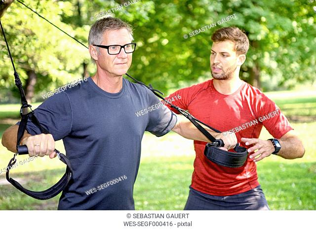 Man doing TRX training while his personal trainer watching him