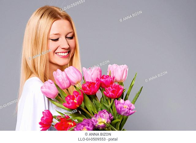 Happy woman holding pink and purple tulips Debica, Poland