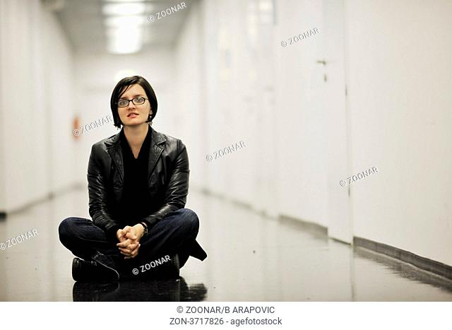 young casual woman sitting and precticing yoga indoor on abstract location