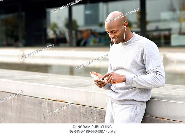 Attractive black man listening to music with headphones in urban background. Male in sportswear outdoors