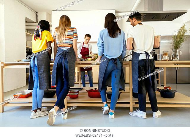 Friends and instructor in a cooking workshop preparing food