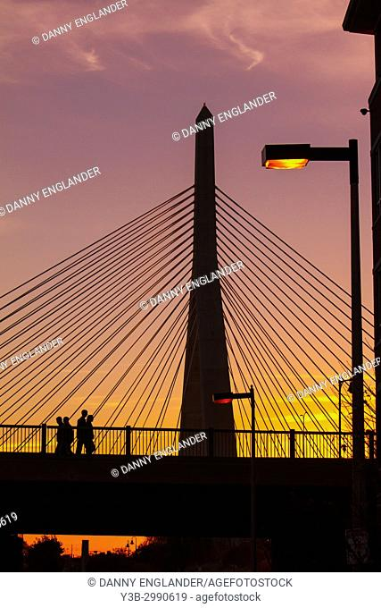 Silhouettes of people at sunset, walking near the Zakim Bridge in Boston, Massachusetts