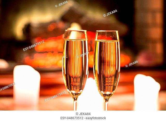 Beautiful two glasses of champagne standing on the table in the background of a blurred room with a decorated Christmas tree and candles. Soft focus