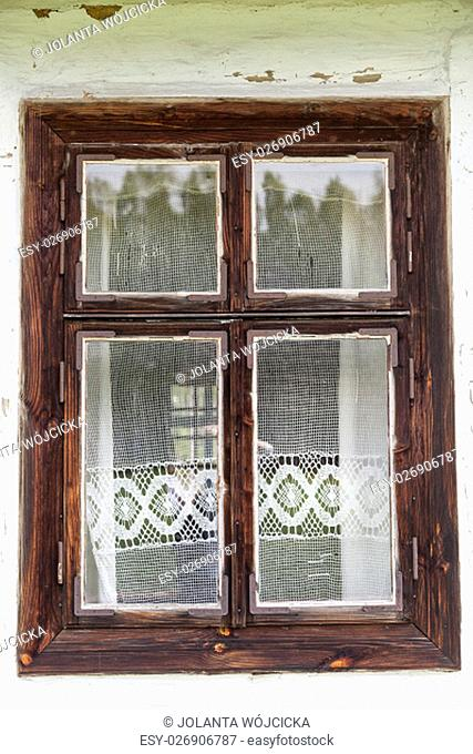 window with lace curtain of old traditional wooden polish cottage in open-air museum, Ethnographic Park, Kolbuszowa, Poland
