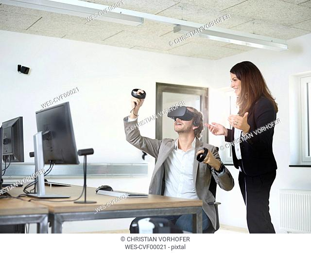Woman with man wearing VR glasses in office