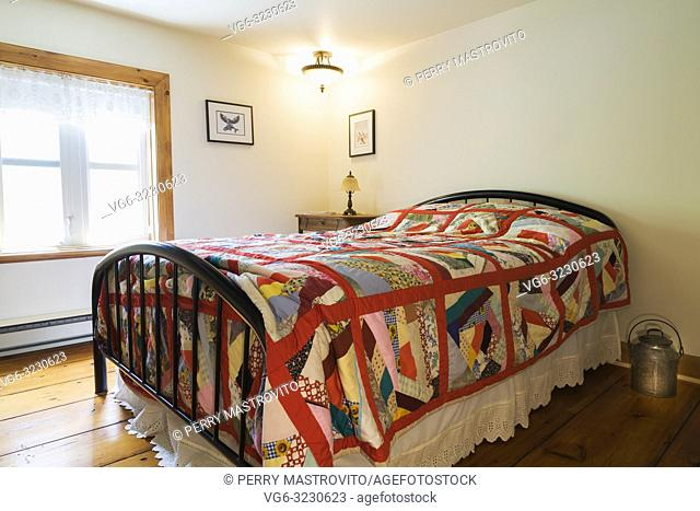Double bed with bright multicoloured patterned bedspread and wrought iron headboard and footboard in upstairs guest bedroom