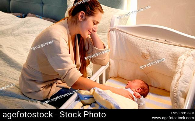 Beautiful smiling young mother rocking crib of her little baby son at night. Concept of happy parenting and family happiness