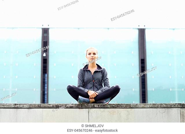 Young, fit and sporty girl sitting on a concrete border. Fitness, sport, urban jogging and healthy lifestyle concept