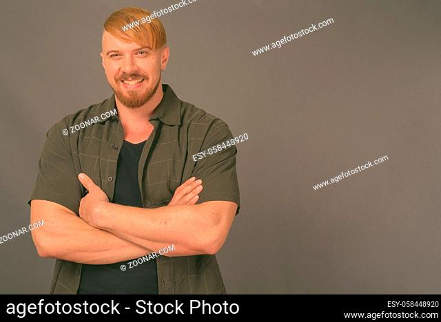 Studio shot of bearded man with blond hair wearing casual clothes against gray background