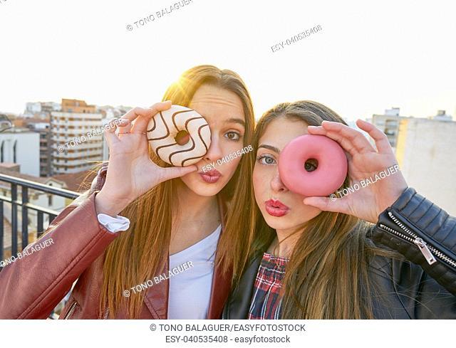 Teen girls portrait with donuts in eye having fun outdoor