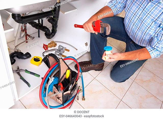 Plumber with Plumbing tools on the kitchen. Renovation