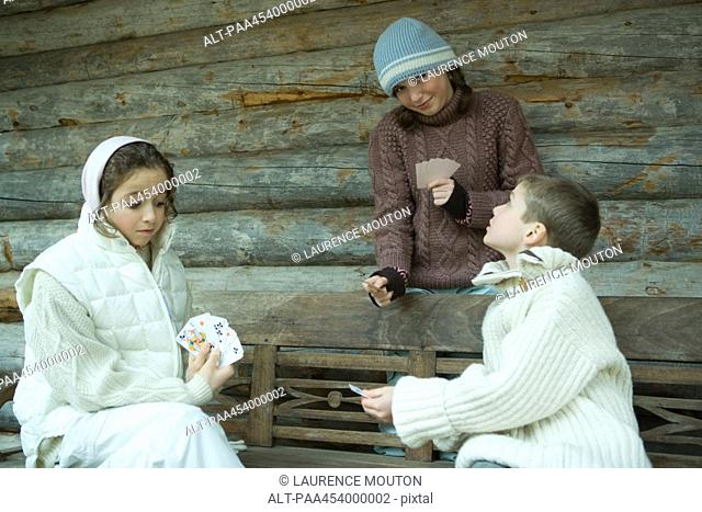 Young friends playing cards outdoors, dressed in winter clothing