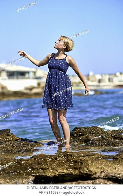 woman dancing at beach, sensitive, enjoying summer breeze, in holiday destination Chersonissos, Crete, Greece