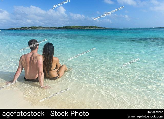 Couple sitting on a white sand beach in the turquoise waters of the Exumas, Bahamas, Caribbean, Central America