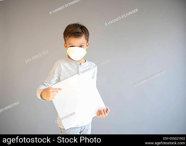 7 year old boy with protective mask holding sign during corona crisis covid 19