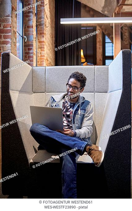 Young man working in creative start-up company, using laptop