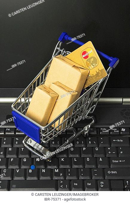 Online shopping, a shopping cart filled with parcel and a credit card standing on the keyboard of a notebook computer
