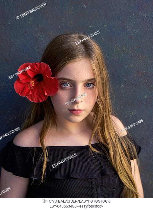 Blond kid girl portrait with hibiscus red flower on hair