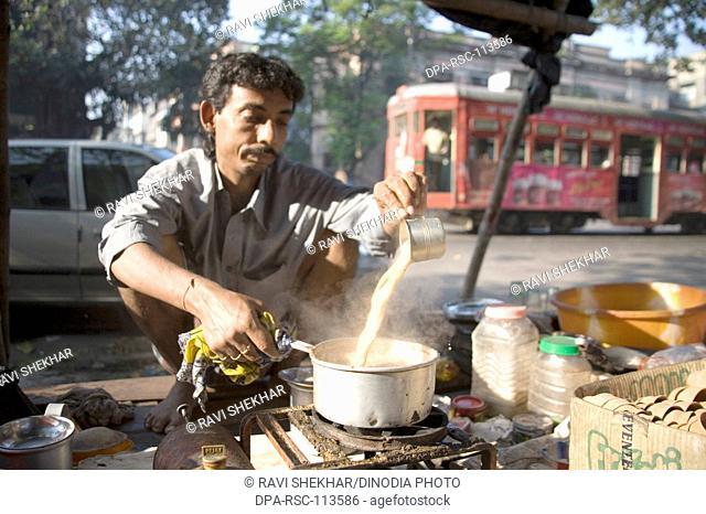 Tea vendor pouring steam tea from cup into teapot ; Calcutta now Kolkata ; West Bengal ; India