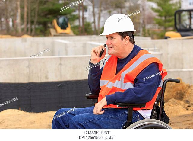 Construction engineer with spinal cord injury on radio at foundation site