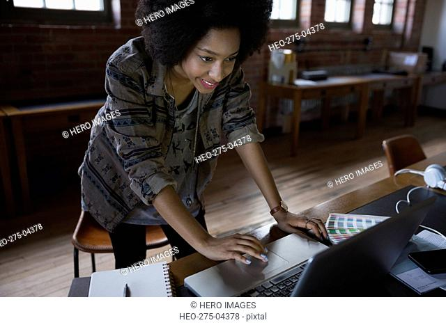 Designer standing working at laptop in office