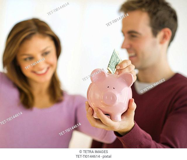 USA, New Jersey, Jersey City, Portrait of young couple putting banknote to piggybank