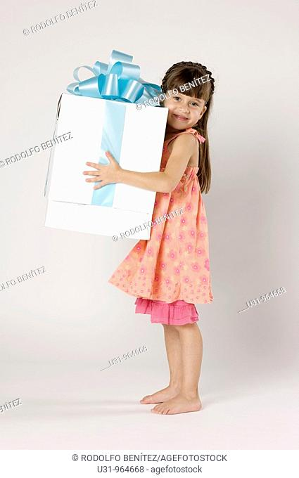 Four year old girl with a big present in a studio setting