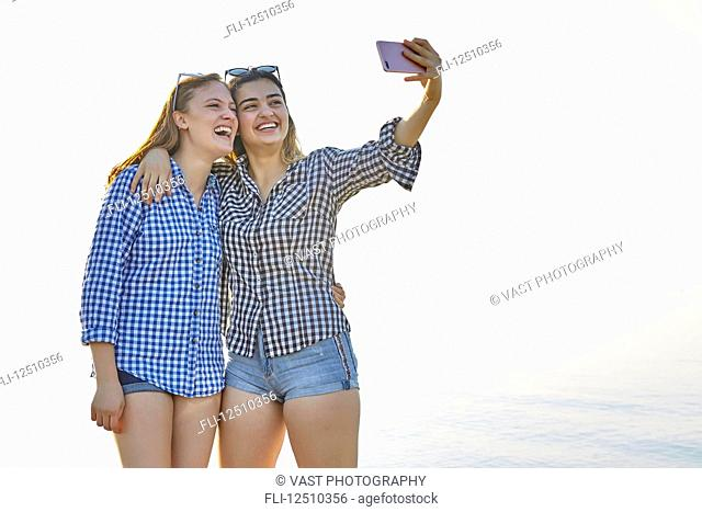 Two teenage girls take a self-portrait as they stand in an embrace at sunset at the lake, Woodbine Beach; Toronto, Ontario, Canada
