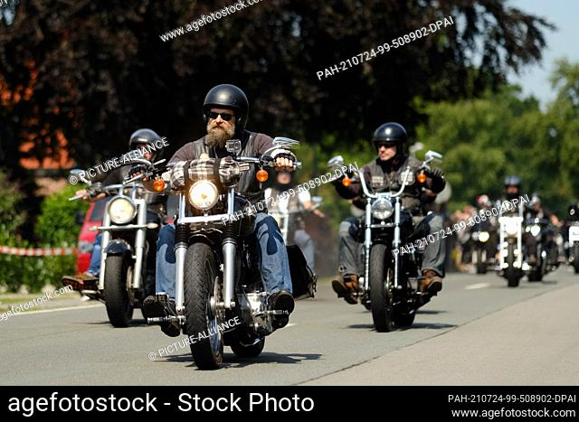 24 July 2021, Lower Saxony, Rhauderfehn: Motorcyclists ride past the house of Kilian, a cancer patient. Several thousand motorcyclists met on Saturday in...