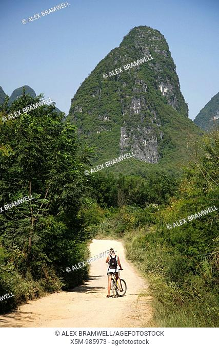 Woman cyclist amongst the Karst Limestone formations of Guangxi Province in China