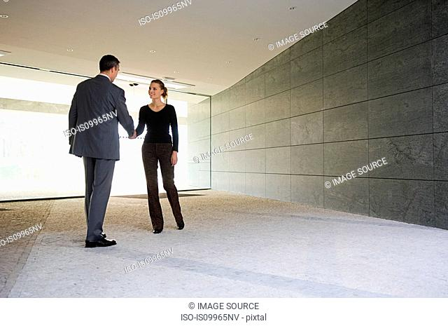 Businesspeople shaking hands in empty office